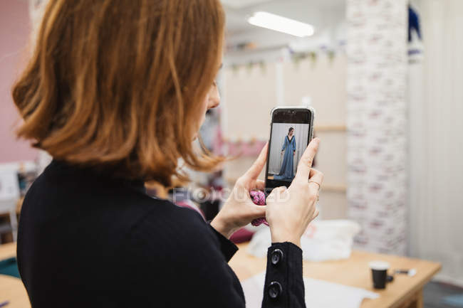 Schneiderin fotografiert Klientin in maßgeschneidertem Kleid für Mappe bei der Arbeit in professioneller Werkstatt — Stockfoto