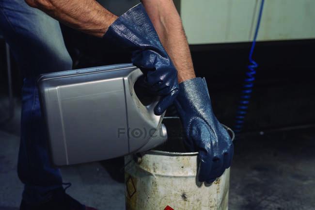 Руки чоловічої праці виливають хімічну рідину з контейнера в металевий барель на фабриці. — стокове фото