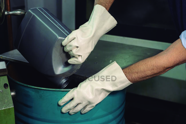 Gloved hands of unrecognizable foreman pouring chemical liquid from canister into metal barrel in factory — Stock Photo