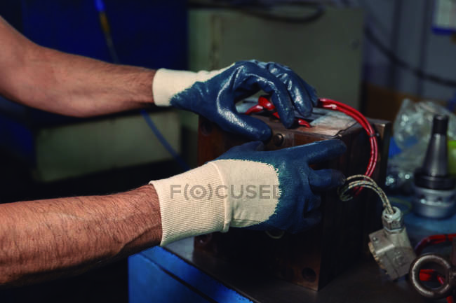 Gloved hands of man building machine on workbench while working in professional workshop — Stock Photo