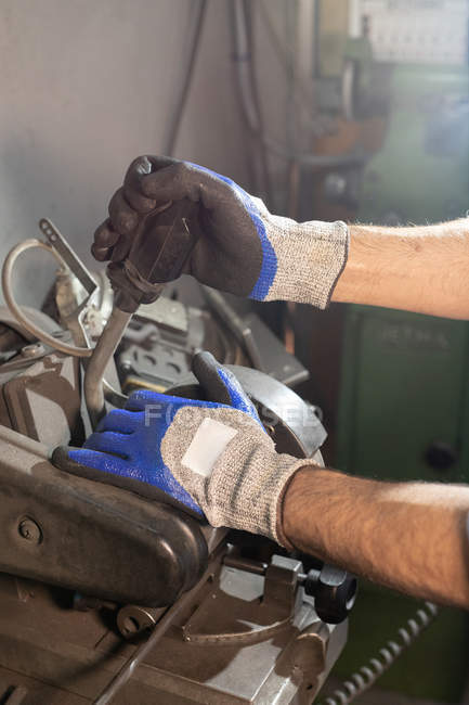 Gloved hands of male creating detail while working on industrial machine at workshop — Stock Photo