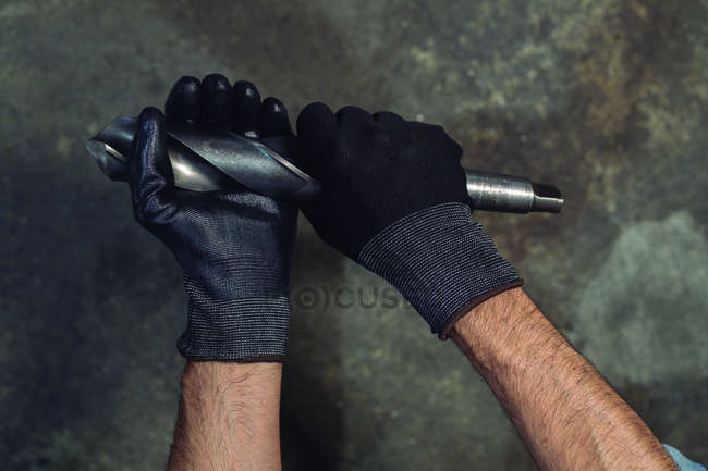 Gloved hands of unrecognizable man swinging drill bit during work process — Stock Photo