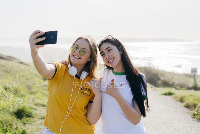 Cheerful girls taking selfie outside — Stock Photo