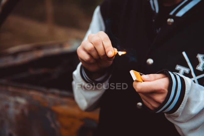 Неузнаваемый человек в повседневной одежде, зажигающий спичку, стоя на размытом фоне старой ржавой машины — стоковое фото