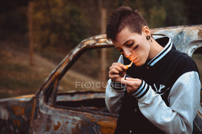 Young female with short hair and painted face lighting cigarette with lighter while standing near old rusty car in countryside — Stock Photo