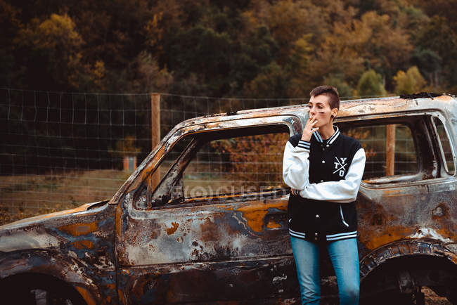 Young female with short hair smoking cigarette while resting near aged burnt vehicle in countryside — Stock Photo
