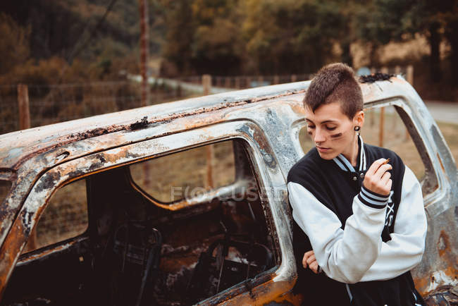 Stylish woman with short hair smoking cigarette while resting near aged burnt vehicle in countryside — Stock Photo