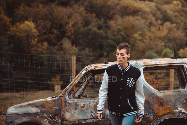Thoughtful young female with short hair walking near aged burnt vehicle in countryside — Stock Photo