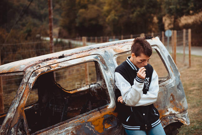 Rebel woman with short hair smoking cigarette near old burnt auto in countryside — Stock Photo