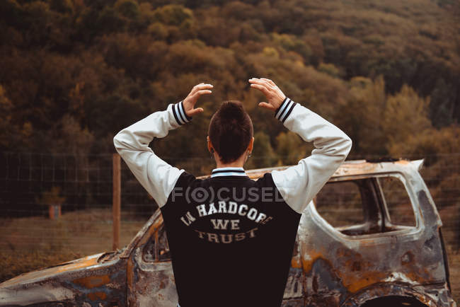 Rear view of female with short hair with raised arms walking near aged burnt vehicle in countryside — Stock Photo