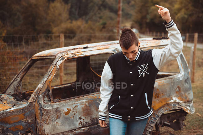 Rude female with short hair smoking cigarette and showing middle finger while walking near aged burnt vehicle in countryside — Stock Photo