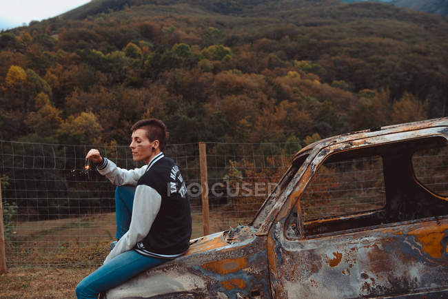 Young woman with short hair holding burning sparkler with closed eyes while sitting on a old rusty vehicle in countryside — Stock Photo