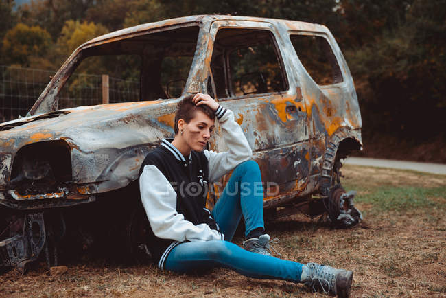 Young female in casual outfit touching short hair and looking away while sitting on ground near old burnt car in countryside — Stock Photo
