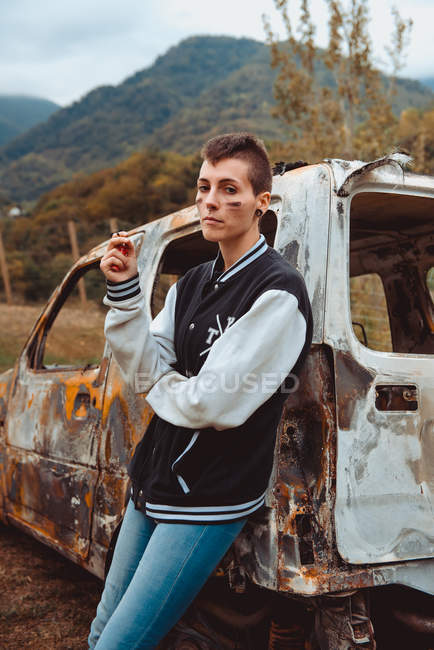Young female with short hair smoking cigarette while resting near aged burnt vehicle in countryside, looking in camera — Stock Photo