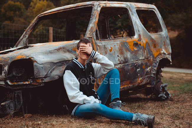 Young female in casual outfit touching and hiding face while sitting on ground near old burnt car in countryside — Stock Photo