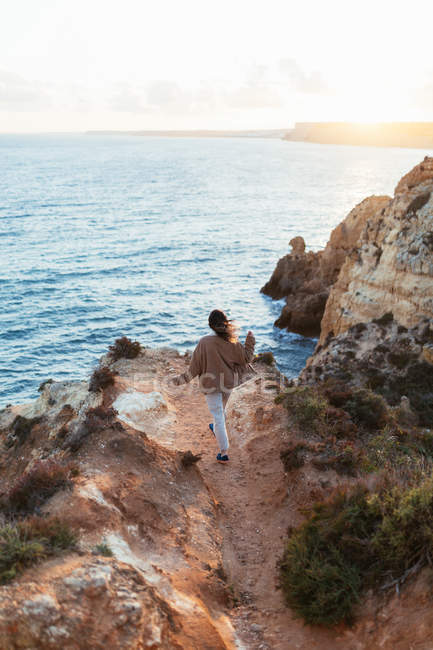Back view of woman in casual clothes walking towards edge of cliff near rippling sea in morning — Stock Photo