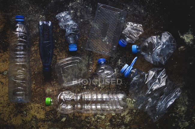 Vista superior de botellas y cajas de plástico dispuestas en suelo contaminado - foto de stock