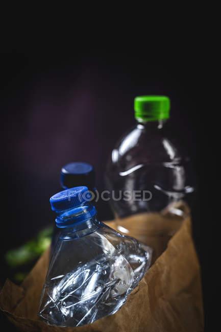 Saco de papel sucio con botellas de plástico desechadas colocadas sobre fondo negro - foto de stock
