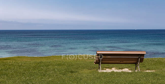 Empty wooden bench standing near edge of shore of blue and peaceful sea surface — Stock Photo
