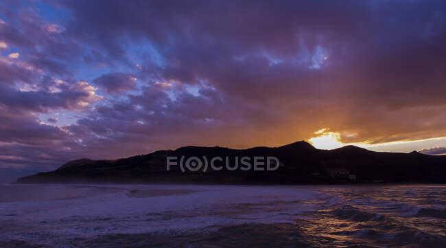 Coucher de soleil incroyable venant sur une île montagneuse reflétée à la surface des eaux sombres de l'océan — Photo de stock