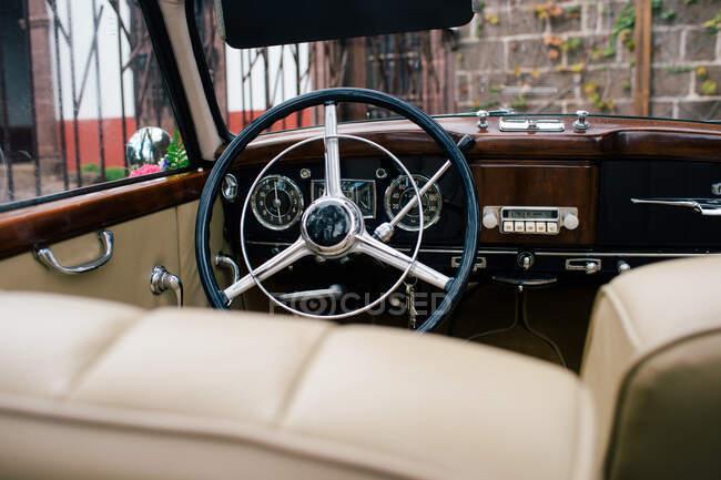 Vista del volante de metal negro y el salpicadero con asientos beige delanteros en el coche clásico - foto de stock