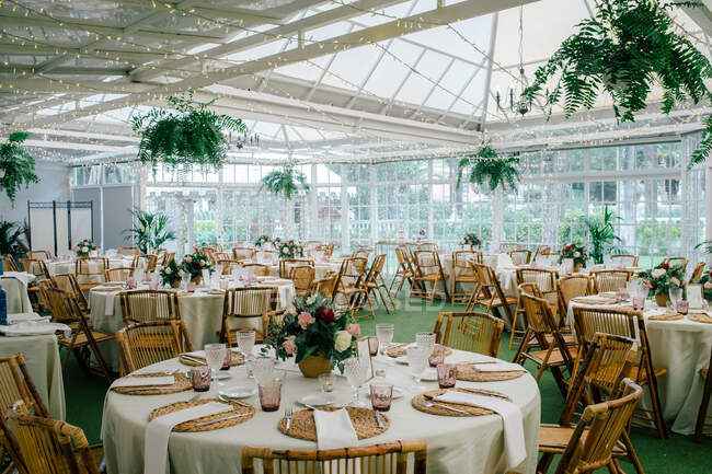 Big spacious room with festive decorated tables and wooden chairs under ceiling with green plants — Stock Photo