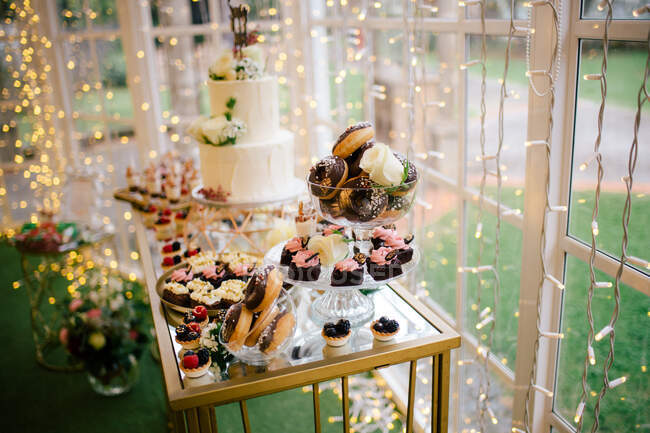 Festive decorated sweet cakes muffins and white flowered cake on stand in restaurant — Stock Photo