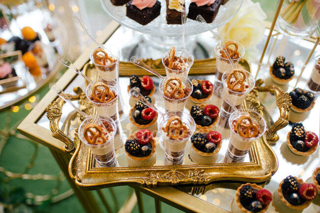From above decorated sweet tasty cheesecake shooters on golden tray and pink flowered cake on glass stand in restaurant — Stock Photo