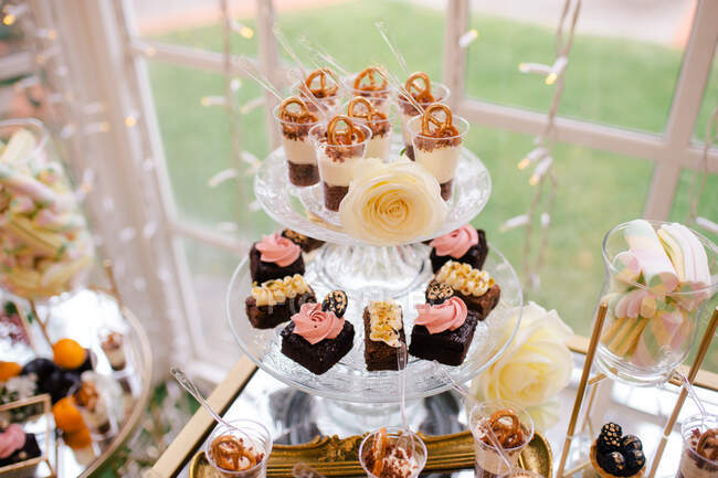 From above sweet delicious creamy chocolate cakes decorated with flowers on glass stand in cafe — Stock Photo
