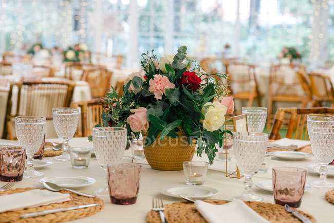 Simple unique flower bouquet in vase on festive decorated table with glassware in restaurant — Stock Photo