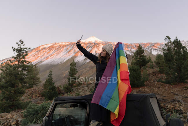 Pleasant woman taking selfie on smartphone with LGBT flag sitting on roof of car — Stock Photo