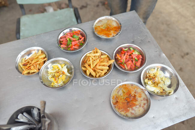 From above appetizing simple dinner with fried potato tomato eggs and soup on metal table in street. Egypt — Stock Photo