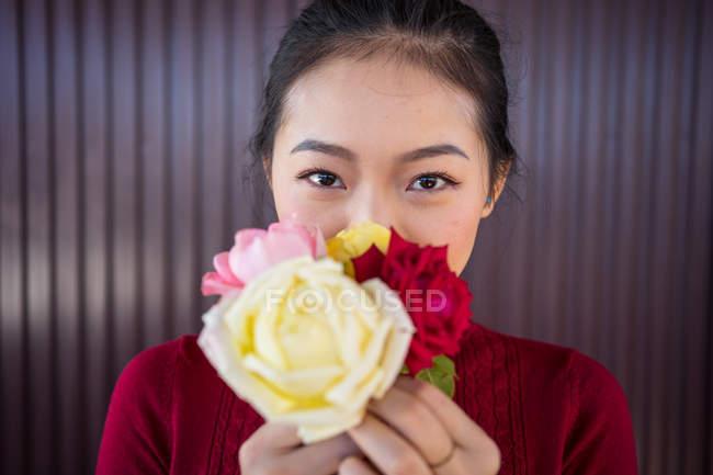 Азиатка, показывающая букет роз на камеру — стоковое фото