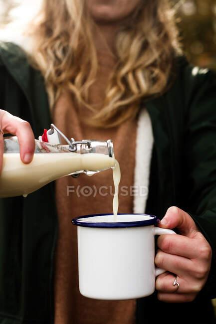 Cultiver femelle dans des vêtements décontractés chauds remplissant tasse en métal blanc avec boisson laitière savoureuse de bouteille en verre tout en ayant pique-nique dans la nature — Photo de stock