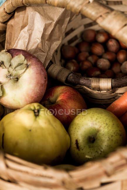 Сверху плетеная корзина со спелыми свежими красочными овощами и фруктами в составе с травами и фундуком, стоящими на земле среди коричневой сухой листвы рядом с теплой голубой клетчатой в осеннем саду — стоковое фото