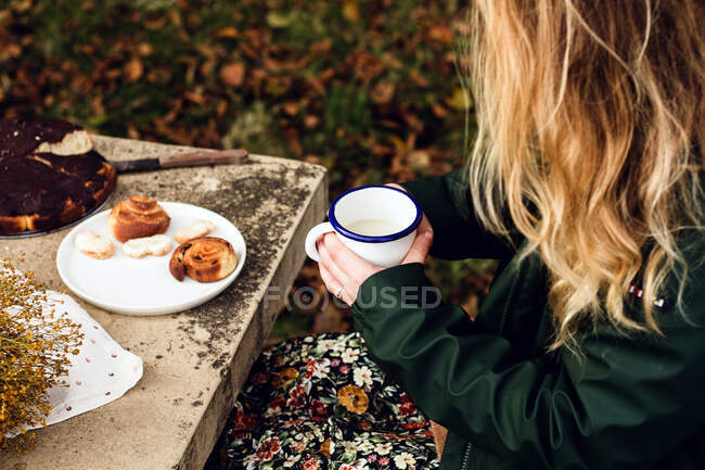 From above crop female in warm casual clothes drinking milk and eating delicious homemade pastry while sitting at gray stone table with bouquet of fresh yellow wildflowers in autumn garden — Stock Photo