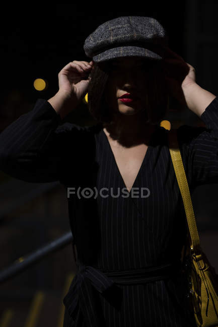 Faceless fashionable woman in black dress with red lipstick and yellow small bag getting into peaky cap at city street on dusk — Stock Photo