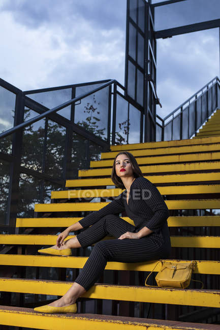 Fashionable woman in black dress with red lipstick and yellow small bag sitting at staircase handrail in a city street on dusk — Stock Photo