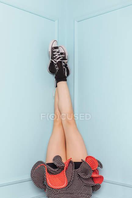 Pernas de uma adolescente de cabeça para baixo em um canto com um vestido de moda em fundo turquesa — Fotografia de Stock
