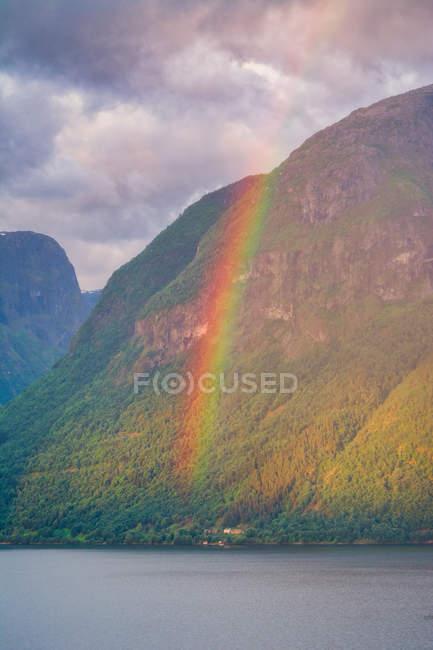 Geheimnisvolle Landschaft von bunten Regenbogen in felsigen Bergen in ruhigem Wasser unter bewölktem Himmel in Norwegen — Stockfoto