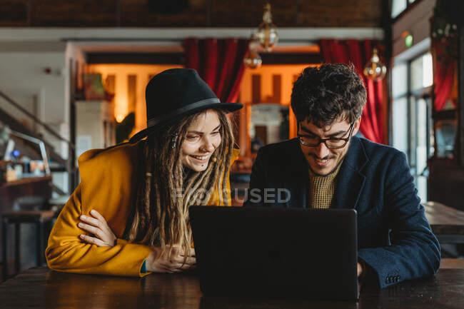 Femme élégante et homme travaillant sur ordinateur portable dans le café — Photo de stock