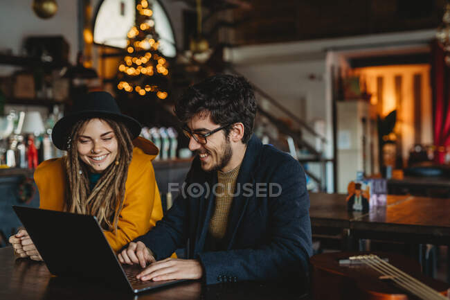 Stylish woman and man working on laptop in cafe — Stock Photo