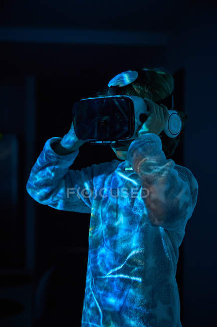 Boy wearing virtual glasses at home in dark with light effects and shadow — стокове фото