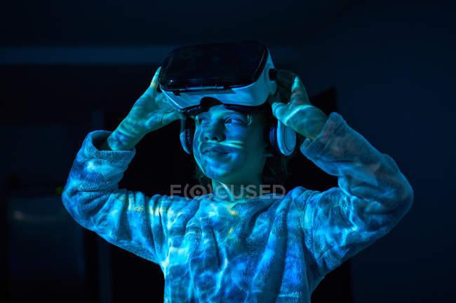 Ребенок снимает виртуальные очки дома в тени — стоковое фото