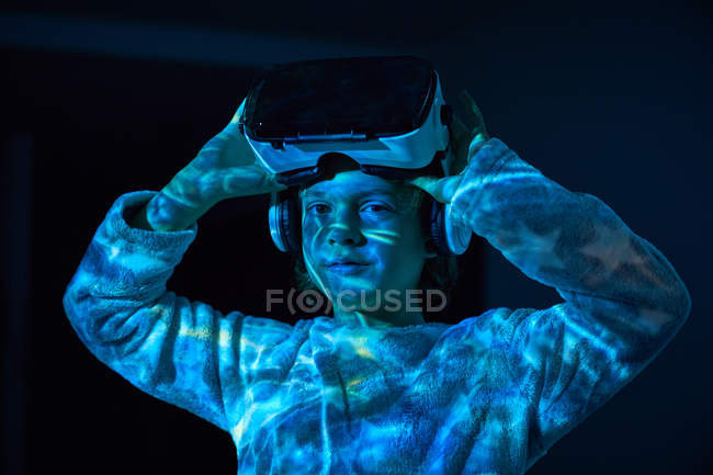 Ребенок снимает виртуальные очки дома в тени, смотрит в камеру — стоковое фото