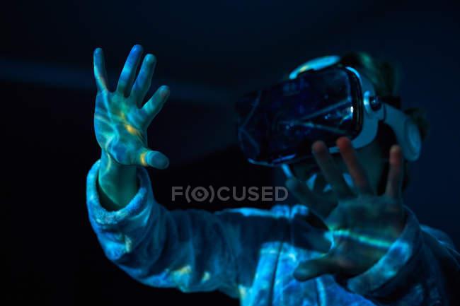 Мальчик в виртуальных очках дома в темноте со световыми эффектами и тенью — стоковое фото
