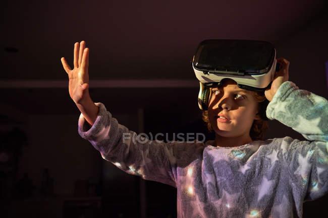 Criança tirando óculos virtuais em casa e brincando com sombra — Fotografia de Stock