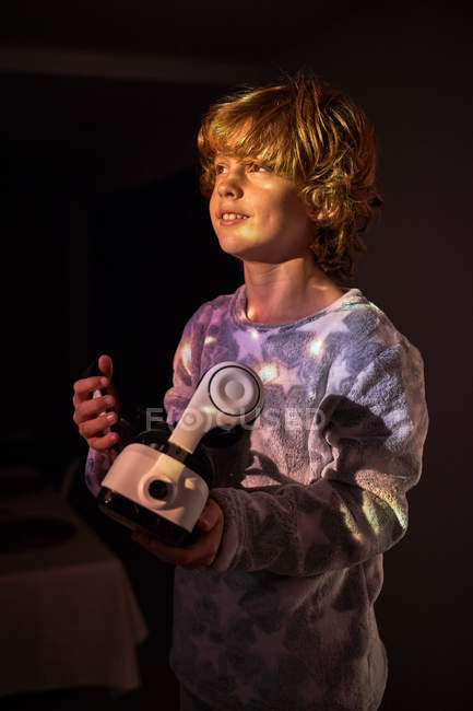 Дитина тримає вдома віртуальні окуляри, озираючись назад. — стокове фото