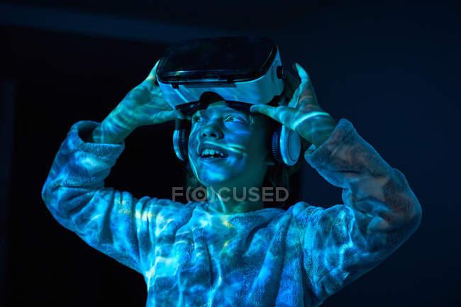 Дитина знімає вдома віртуальні окуляри і озирається. — стокове фото