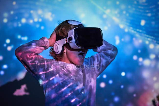 Grundschulkind trägt zu Hause virtuelle Brille mit farbigen Lichteffekten — Stockfoto